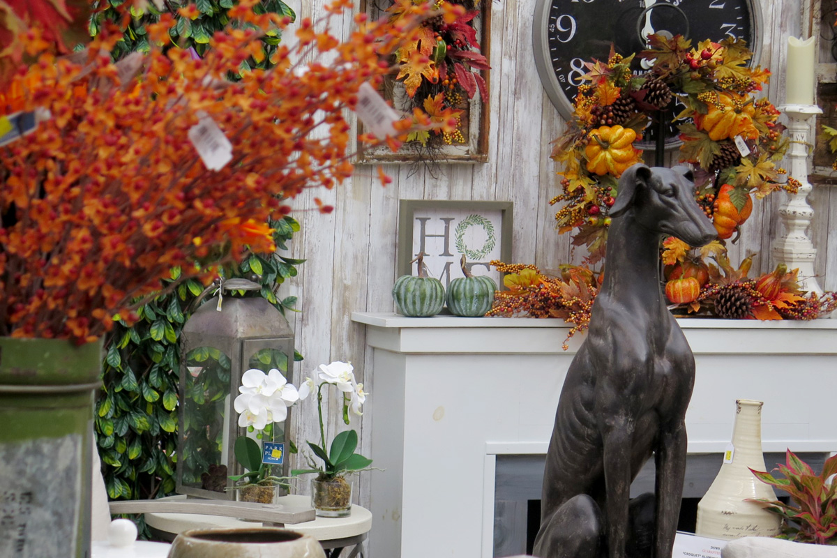 Dog statue with faux flowers and leaves
