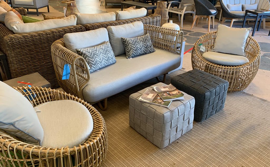 Rattan outdoor seating group featuring two chairs and a loveseat